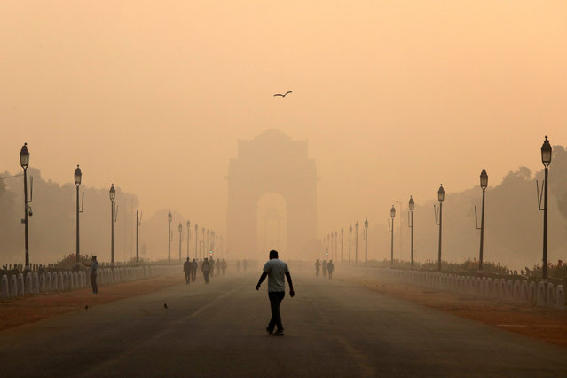 A man walks in front of the India Gate shrouded in smog in New Delhi, India, October 29, 2018. (Photo by Anushree Fadnavis/Reuters)