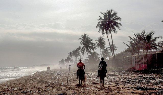 People ride horses on a beach in Abidjan, Ivory Coast on July 28, 2021. (Photo by Mehmet Kaman/Anadolu Agency via Getty Images)