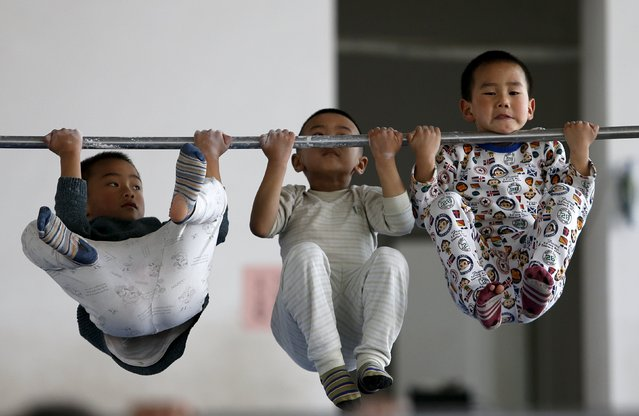 Young gymnasts practice pull-up on a bar at a gymnasium of a sports school in Jiaxing, Zhejiang province April 11, 2015. (Photo by William Hong/Reuters)