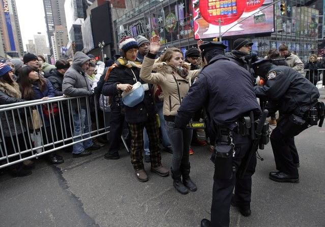New York City police officers search people entering barricaded pens used to control crowds in Times Square in preparation for the ball drop on New Year's Eve, Tuesday, December 31, 2013, in New York. (Photo by Kathy Willens/AP Photo)