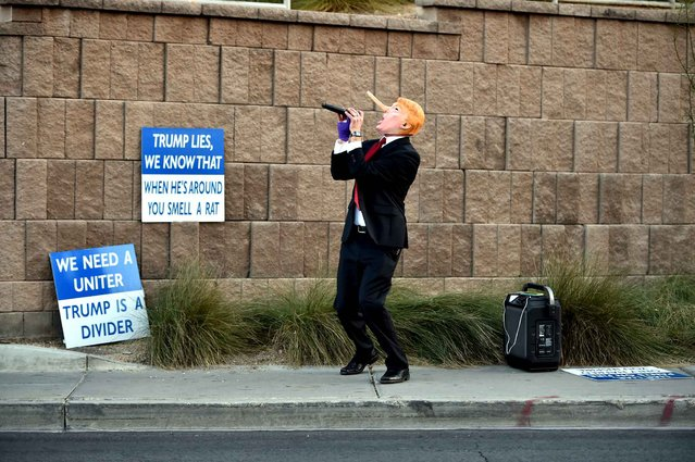 """Gil Mobley wears a Donald Trump costume while singing a song about him while protesters rally in front of the Trump Hotel in Las Vegas, Nevada on February 23, 2016. US Republican presidential candidates face off in Nevada as frontrunner Donald Trump tries to maintain momentum with a rousing victory in the last contest before next week's all-important """"Super Tuesday"""" votes. (Photo by Josh Edelson/AFP Photo)"""