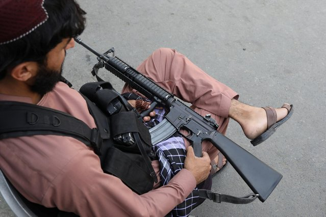 A member of the Taliban sits while holding his gun in Kabul, Afghanistan on September 4, 2021. (Photo by WANA (West Asia News Agency) via Reuters)
