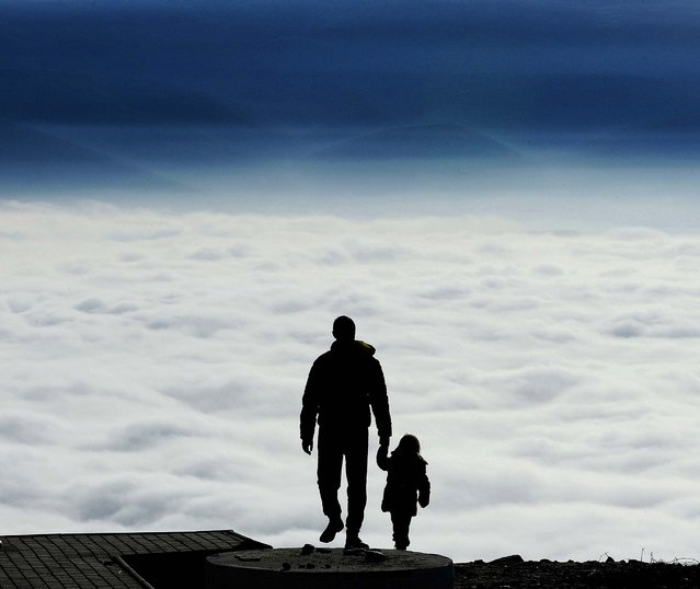 A man with a child walks towards the top of Vodno Mountain in Skopje, Macedonia, on January 9, 2014. (Photo by Boris Grdanoski/Associated Press)