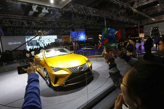 Visitors take photos of a Lexus car on display at the 16th Shanghai International Automobile Industry Exhibition in Shanghai, China, 20 April 2015. (Photo by How Hwee Young/EPA)
