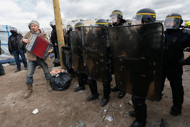 "A man plays music in front of French riot policemen after authorities started to clear a part of the migrant camp called ""Jungle"" in Calais, France, 29 February 2016. French authorities began dismantling part of the migrant camp near Calais, after an expulsion order issued by the local administration was upheld by a judge last week. (Photo by Laurent Dubrule/EPA)"