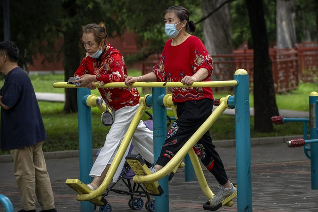A woman wearing a face mask to protect against COVID-19 uses an exercise machine at a public park in Beijing, Thursday, September 9, 2021. (Photo by Mark Schiefelbein/AP Photo)