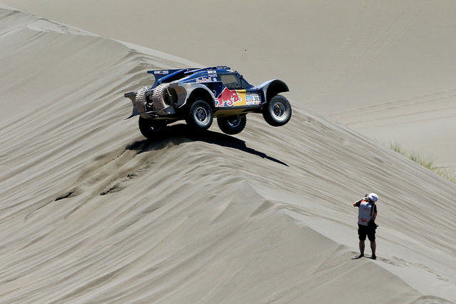 Buggy driver Carlos Sainz of Spain and co-pilot Timo Gottschalk of Germany race in the dunes during the second stage of the Dakar Rally between the cities of San Luis and San Rafael in San Rafael, Argentina, Monday  January 6, 2014. This is the sixth consecutive year the race has been run in South America, and the first time Bolivia has been on the route. (Photo by Victor R. Caivano/AP Photo)