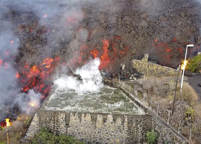 Hot lava reaches a balsa normally used for for irrigation after an eruption of a volcano on the island of La Palma in the Canaries, Spain, Monday September 20, 2021. (Photo by Europa Press via AP Photo)