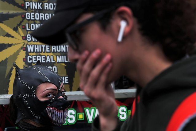 A woman dressed in costume looks on, amid the coronavirus disease (COVID-19) pandemic, as others arrive for the 2021 New York Comic Con at the Jacob Javits Convention Center in New York City, U.S., October 8, 2021. (Photo by Shannon Stapleton/Reuters)