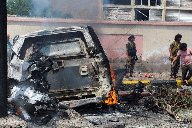 Policemen stand at the scene of a blast in Aden, Yemen, October 10, 2021. (Photo by Fawaz Salman/Reuters)