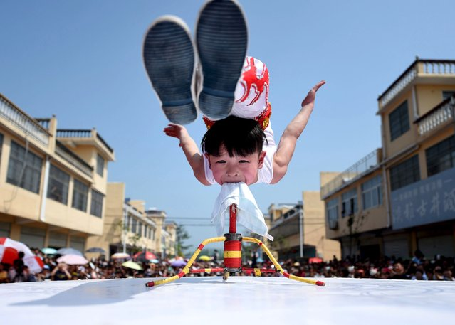A six-year-old acrobat performs on the opening of a tourist festival in Bozhou, Anhui province, China May 3, 2015. (Photo by Reuters/China Daily)