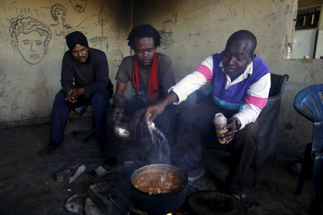 Sudanese immigrants cook food in their shelter in the western Greek town of Patras May 4, 2015. (Photo by Yannis Behrakis/Reuters)