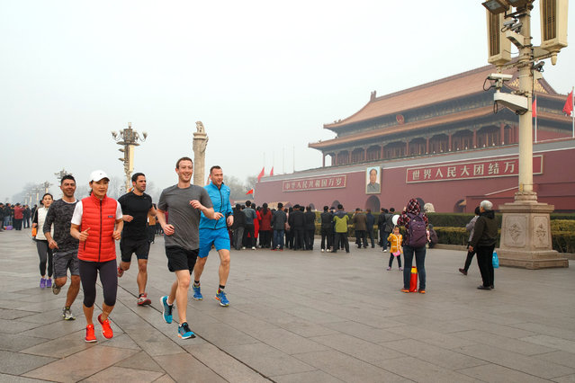 This handout picture taken and provided by Facebook on March 18, 2016, shows Facebook CEO Mark Zuckerberg (front R, grey shirt) running past Tiananmen Gate, the entrance to the Forbidden City, in Beijing. Facebook CEO Mark Zuckerberg took a mask-free jog through Beijing's Tiananmen Square on March 18, smiling through thick smog as he seeks greater access for his company to China, where its service is banned. Some Chinese see it as a publicity stunt for Facebook, but they doubt it's working for Zuckerberg. (Photo by AFP Photo/Stringer)