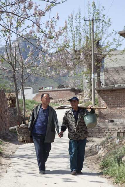 In this April 23, 2015 photo, friends Jia Wenqi, left, and Jia Haixia walk along a lane in Yeli village near Shijiazhuang city in northern China's Hebei province. (Photo by Helene Franchineau/AP Photo)