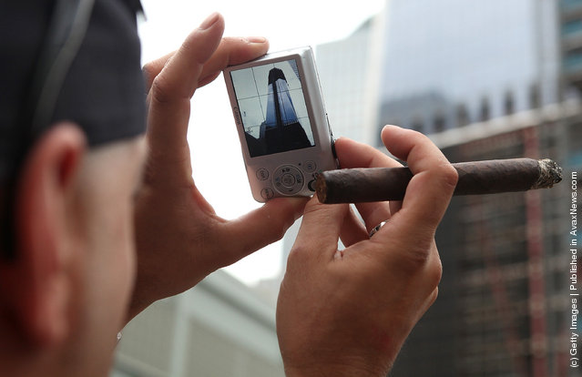 A man takes a photo of One World Trade at the World Trade Center site on September 10, 2011 in New York City