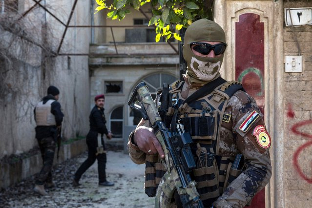 In this Tuesday, February 21, 2017 photo, a masked Iraqi security officer stands guard outside a house during a raid on suspected Islamic State group fighters, in Mosul, Iraq. (Photo by John Beck/AP Photo)