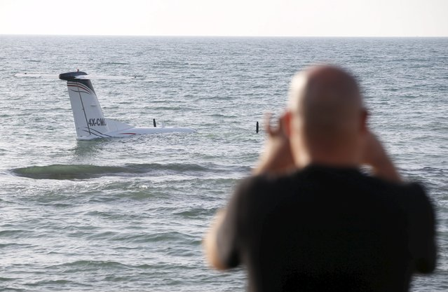 A man takes a photo with his cell phone of an airplane that made an emergency landing in the waters of the Mediterranean sea off the shore of Tel Aviv, Israel, April 3, 2016. (Photo by Baz Ratner/Reuters)