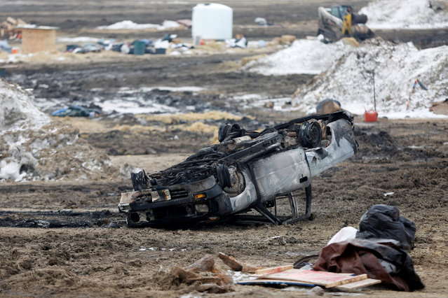 A burned car rests on its roof in the main opposition camp against the Dakota Access oil pipeline near Cannon Ball, North Dakota, U.S., February 23, 2017. (Photo by Terray Sylvester/Reuters)