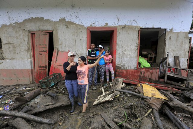 Residents stand in front of their damaged house, after a landslide close to the municipality of Salgar in Antioquia department, Colombia May 19, 2015. (Photo by Jose Miguel Gomez/Reuters)