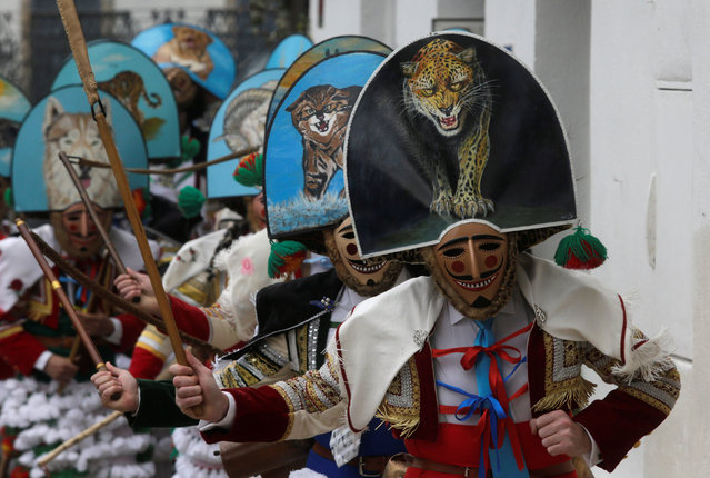 "Carnival revellers dressed as ""Peliqueiros"" run along a street in the village of Laza, Spain February 26, 2017. ""Peliqueiros"", or ancient tax collectors, pursued villagers through the streets ringing their cowbells and hitting villagers with their sticks. (Photo by Miguel Vidal/Reuters)"