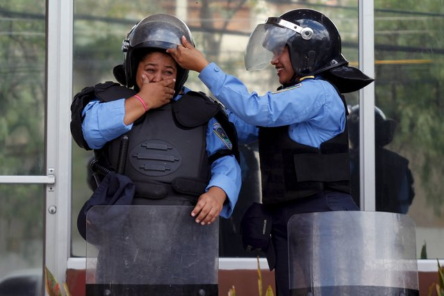 A policewoman helps a colleague to adjust her helmet during a protest to demand justice for slain journalists in Tegucigalpa, Honduras, April 11, 2016. (Photo by Jorge Cabrera/Reuters)