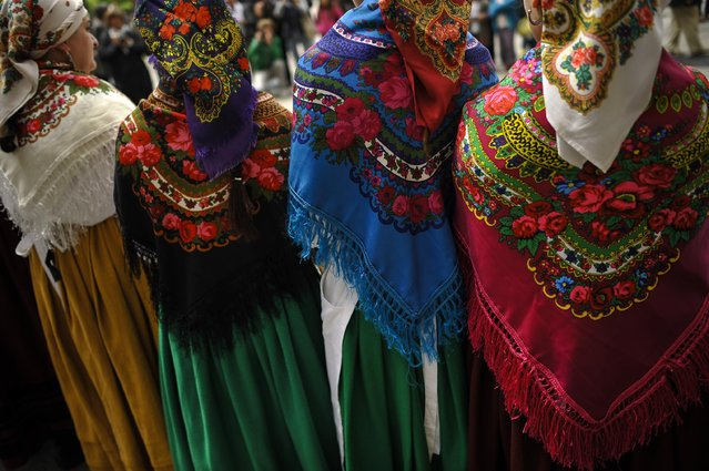 A group of regional dancers cover their heads with shawls as they take part in a dance, in Plaza del Castillo square,  in Pamplona, northern Spain, Saturday, May 23, 2015. With a rich traditions on dress and regional music, a lot of regional groups perform on the street during spring season. (Photo by Alvaro Barrientos/AP Photo)