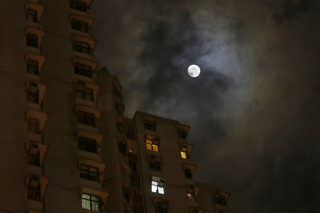 A full moon rises over a building, a day before the Mid-Autumn Festival in Hong Kong, Wednesday, September 18, 2013. (Photo by Vincent Yu/AP Photo)