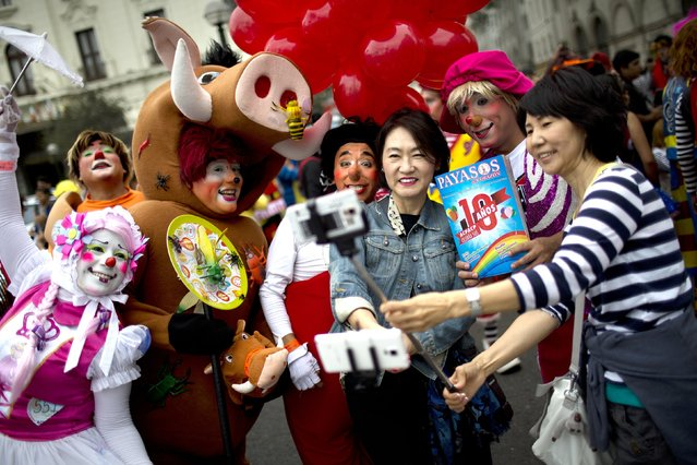 Tourist Gina Youginkim, right, and Margaret Kahng, from South Korea, third from right, pose for a picture with clowns during a march commemorating the Peruvian clown day in Lima Peru, Monday, May 25, 2015. (Photo by Rodrigo Abd/AP Photo)