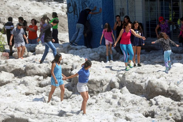 Residents play on top of ice after a heavy storm of rain and hail which affected some areas of the city in Guadalajara, Mexico on June 30, 2019. (Photo by Fernando Carranza/Reuters)