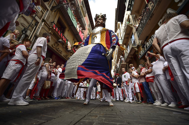 A giant member of San Fermin Comparsa Parade take part in a procession at the San Fermin Festival in Pamplona, northern Spain, Sunday, July 7, 2019. Revellers from around the world flock to Pamplona every year to take part in the eight days of the running of the bulls. (Photo by Alvaro Barrientos/AP Photo)
