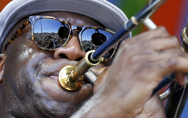 The crowd is reflected in the sunglasses of Big Sam, of Big Sam's Funky Nation, as he performs at the New Orleans Jazz and Heritage Festival in New Orleans, Saturday, April 23, 2016. (Photo by Gerald Herbert/AP Photo)
