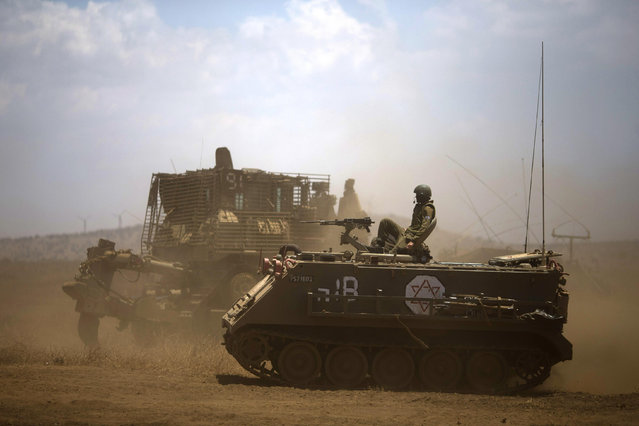 Israeli soldiers drive armored military vehicles during training exercises in the Israeli-occupied Golan Heights, near the border with Syria, Wednesday, June 17, 2015. Syrian rebels launched a wide-ranging offensive against Syrian government positions near the Golan Heights on Wednesday, after tit-for-tat shelling in and around Damascus left at least 33 people dead, activists said. Insurgents have been on the offensive in southern Syria for the past three months, capturing military bases, villages and a border crossing point with Jordan. (AP Photo/Ariel Schalit)