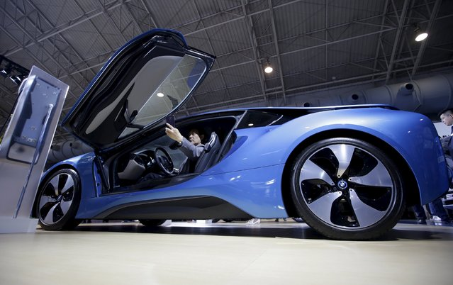 """A visitor takes a """"selfie"""" in a new BMW i8 plug-in hybrid sports car during the Auto China 2016 in Beijing, China, April 25, 2016. (Photo by Jason Lee/Reuters)"""