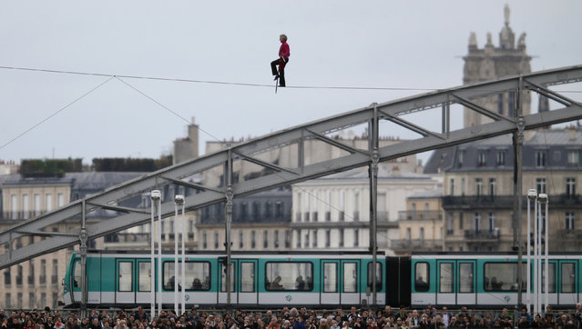French acrobat Denis Josselin balances on a tightrope as he crosses the Seine river in front of the Austerlitz bridge in Paris, April 6, 2014. (Photo by Christian Hartmann/Reuters)