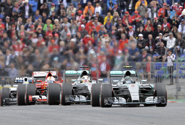 Mercedes driver Nico Rosberg, right, of Germany steers his car in front of Mercedes driver Mercedes driver Lewis Hamilton of Britain, center and Ferrari driver Sebastian Vettel of Germany during the Austrian Formula One Grand Prix race at the Red Bull Ring  in Spielberg, southern Austria, Sunday, June 21, 2015. (AP Photo/Kerstin Joensson)