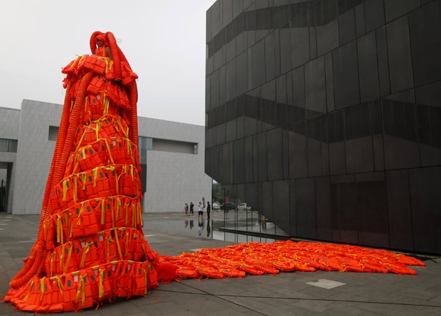 "A new artwork entitled ""Jumping Orange"" by artist Kong Ning, which consists of 443 life jackets, is seen at a yard of an art gallery in Beijing, China, June 27, 2015. Kong Ning said she was motivated to create this piece after a cruise ship capsized in the Yangtze River earlier this month, and covered the life jackets with yellow ribbons to commemorate the victims of the accident. (Photo by Kim Kyung-Hoon/Reuters)"