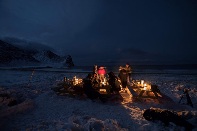 Surfers rest in front of a camp fire after an evening of surfing in Unstad along the northern Atlantic Ocean on March 12, 2017, where the water temperatures is at five degrees centigrade and the air temperature is at minus two degrees centigrade. (Photo by Olivier Morin/AFP Photo)