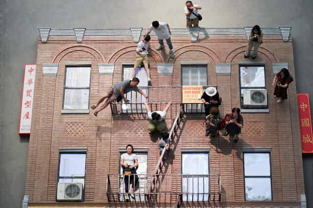 """People interact with one of the pieces on display at an exhibition by Argentina artist Leandro Erlich entitled """"The Confines of the Great Void"""" at the CAFA Art Museum in Beijing on July 23, 2019. (Photo by Wang Zhao/AFP Photo)"""