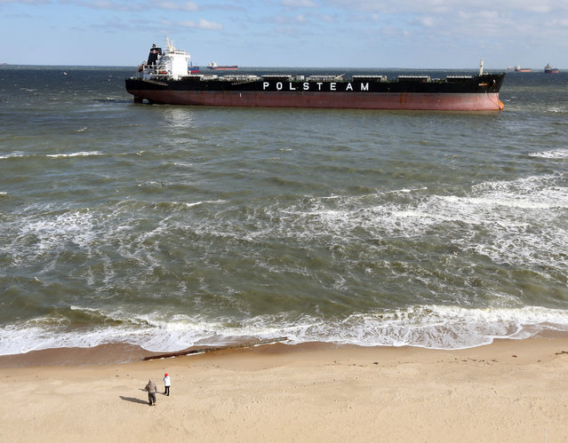 People walk along the beach Wednesday, April 16, 2014, near where the 751-foot bulk carrier Ornak ran aground Tuesday night in the lower Chesapeake Bay, in Virginia Beach, Va. There were no reports of injuries, damage or pollution from the grounding, and the vessel was not blocking other water traffic, said Coast Guard spokesman Petty Officer First Class Brandyn Hill. (Photo by Steve Earley/AP Photo/The Virginian-Pilot)