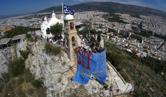 """Supporters of the No vote hang a banner reading in Greek and English """"NO to austerity and fear"""" referring to the upcoming referendum atop of Lycabettus hill in Athens, Thursday, July 2, 2015. The battle for Greek votes entered full swing Thursday ahead of a crucial weekend referendum that could decide whether the country falls out of the euro. (Photo by Antonis Nikolopoulos/Eurokinissi via AP Photo)"""