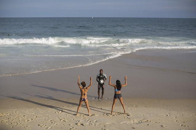Rocinha Surf Association, ASR, teacher Carlos Belo, center, exercises young students before entering the water at Sao Conrado brach in Rio de Janeiro, Brazil, Thursday, July 2, 2015. (Photo by Felipe Dana/AP Photo)