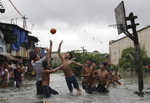 Filipino boys play basketball in floodwaters from a swollen creek at a coastal village in Malabon, north of Manila, Philippines, Wednesday, July 8, 2015. Typhoon Chan-Hom passing over the northeastern waters of the Philippines heading to northern Taiwan has enhanced the seasonal monsoon, dumping heavy rains over the capital, Manila, and the northern provinces. (Photo by Aaron Favila/AP Photo)