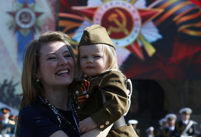 A woman and a girl dressed in historical Red Army uniform, wait before watching the Victory Day parade, marking the 71st anniversary of the victory over Nazi Germany in World War Two, at Red Square in Moscow, Russia, May 9, 2016. (Photo by Grigory Dukor/Reuters)