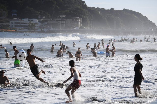 People enjoy the beach near Enoshima Island (in background) on the coast of Kanagawa prefecture, southwest of Tokyo, on August 13, 2019. (Photo by Charly Triballeau/AFP Photo)