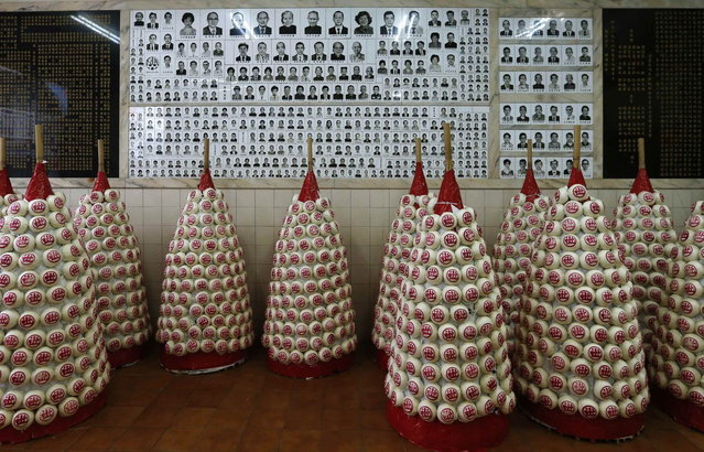 "Small ""bun mountains"" are displayed in front of former donors, most of whom have deceased, inside a community centre at Hong Kong's Cheung Chau island April 30, 2014, six days before the annual Bun Festival. The festival celebrates the islanders' deliverance from famine many centuries ago and is meant to placate ghosts and restless spirits. (Photo by Bobby Yip/Reuters)"