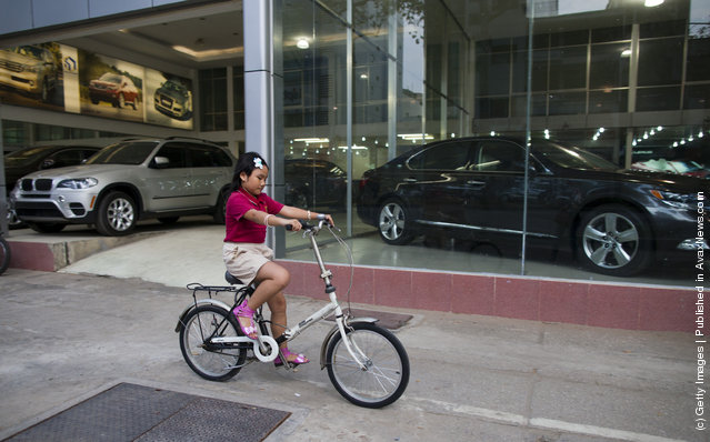 A Vietnamese girl rides her bicycle by a luxury car showroom