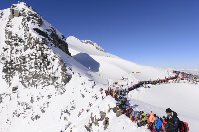 Competitors climb on their way to Rosablanche pass, near Verbier, Switzerland, during the Glacier Patrol race Sunday 04, Mai, 2014. The Glacier Patrol (Patrouille des Glaciers) organized by the Swiss Army sees highly-experienced hiker-skiers trek across the Haute Route along the Swiss-Italian border from Zermatt to Verbier. The race covers 53km (31.8 miles) by foot and ski, with over 7000m gain and descent along the way. (Photo by Anthony Anex/EPA)