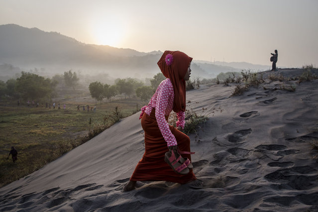 An Indonesian muslim woman walks on 'sea of sands' as they prepare for Eid Al-Fitr prayer at Parangkusumo beach on July 17, 2015 in Yogyakarta, Indonesia. (Photo by Ulet Ifansasti/Getty Images)