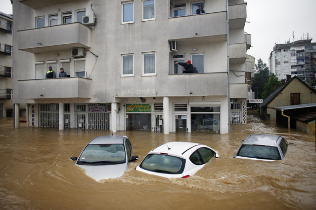 People stand in their apartments as they wait to be evacuated in the flooded town of Obrenovac, southwest of Belgrade, May 17, 2014. (Photo by Marko Djurica/Reuters)