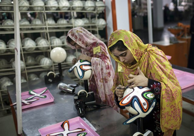 An employee adjusts outer panels on a soccer ball inside the soccer ball factory that produces official match balls for 2014 World Cup in Brazil, in Sialkot, Punjab province May 16, 2014. (Photo by Sara Farid/Reuters)